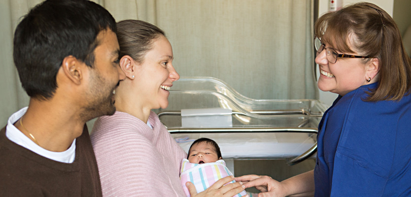 Family with newborn baby and midwife