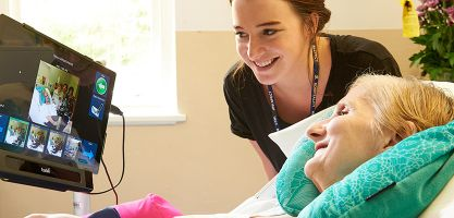 Young nurse helping patient with assisted technology