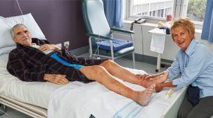 Patient receiving foot massage in hospital bed