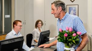 Visitor bringing flowers to patient at hospital
